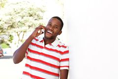 Smiling young black standing outside and talking on mobile phone Stock Photo