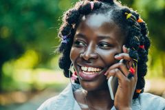 Portrait of an African beauty smiling young black woman in the park with a solar flare talking on the phone royalty free stock image