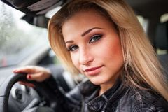 Portrait of smiling young blond woman in car. Stock Photo