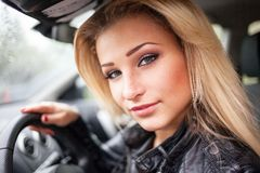 Portrait of smiling young blond woman in car. Stock Photos