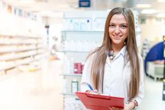 Portrait of smiling young blonde pharmacist at drug store Stock Image