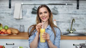 Portrait of smiling young blonde woman drinking fresh orange juice. Medium shot on RED camera