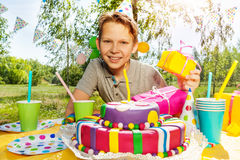Portrait of smiling young boy with birthday gifts. Portrait of happy smiling boy with birthday gifts, sitting next to the birthday cake at the outdoor party Royalty Free Stock Photography