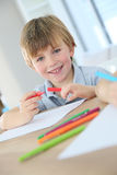 Portrait of a smiling young boy drawing Stock Image