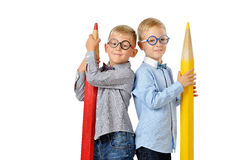 Portrait smiling young boys in glasses and bowtie posing near huge colorful pencils. Educational concept. Isolated over white. Royalty Free Stock Images