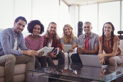 Portrait of smiling young business people sitting on sofa Royalty Free Stock Photos