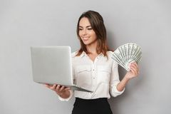 Portrait of a smiling young business woman. Looking at laptop computer while showing bunch of money banknotes isolated over white background Stock Photos