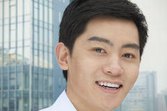 Portrait of smiling young businessman close-up, outdoors with building exterior, Beijing, China Royalty Free Stock Images