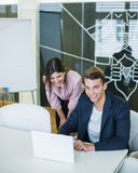 Portrait of smiling young businessman with female colleague using laptop at table in office Royalty Free Stock Photos