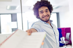 Portrait of smiling young businessman giving document in office Royalty Free Stock Image
