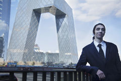 Portrait of smiling young businessman leaning on the railing with the CCTV building in background, Beijing Stock Photos