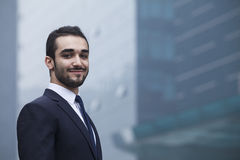 Portrait of smiling young businessman, outdoors, business district Royalty Free Stock Image