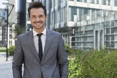Portrait of smiling young businessman standing against office building Royalty Free Stock Photography