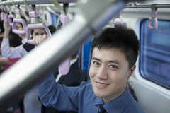 Portrait of smiling young businessman standing on the subway, looking at camera Stock Images