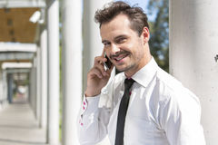 Portrait of smiling young businessman using cell phone outside office Royalty Free Stock Photos