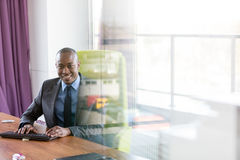 Portrait of smiling young businessman using computer keyboard at desk in office Royalty Free Stock Images