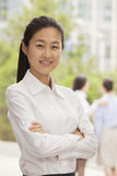 Portrait of smiling young businesswoman with arms crossed, Beijing Royalty Free Stock Image