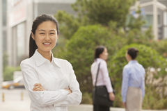 Portrait of smiling young businesswoman with arms crossed, Beijing Stock Image