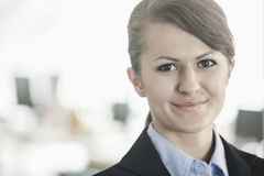 Portrait of smiling young businesswoman with bangs looking at the camera, head and shoulders stock photography