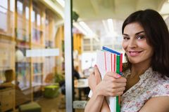 Portrait of smiling young businesswoman with books in office Stock Image
