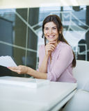 Portrait of smiling young businesswoman with documents at conference table Stock Photos