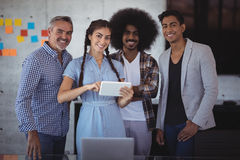 Portrait of smiling young businesswoman explaining over digital tablet to colleagues Royalty Free Stock Photo