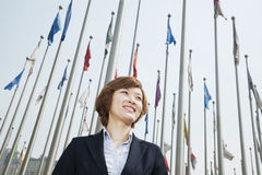 Portrait of smiling young businesswoman with flags Stock Images