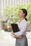 Portrait of smiling young businesswoman holding file and looking up, outdoors, Beijing Royalty Free Stock Image