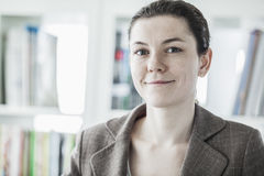 Portrait of smiling young businesswoman looking at the camera, head and shoulders Stock Image