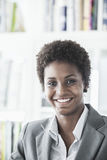 Portrait of smiling young businesswoman with short hair looking at the camera, head and shoulders Royalty Free Stock Images