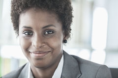 Portrait of smiling young businesswoman with short hair looking at the camera, head and shoulders Royalty Free Stock Photo