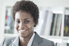 Portrait of smiling young businesswoman with short hair looking at the camera, head and shoulders Stock Images
