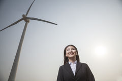 Portrait of smiling young businesswoman standing by a wind turbine Royalty Free Stock Photos