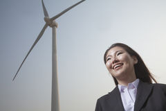 Portrait of smiling young businesswoman standing by a wind turbine Royalty Free Stock Image