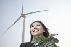 Portrait of smiling young businesswoman standing by a wind turbine and holding a plant Royalty Free Stock Photography