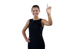 Portrait of smiling young businesswoman touching invisible interface Stock Image
