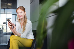 Portrait of smiling young businesswoman using mobile phone on chair in office Stock Images