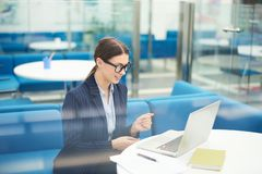 Young Businesswoman in Internship. Portrait of smiling young businesswoman wearing glasses using laptop in office during internship in corporate enterprise, copy stock image