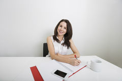 Portrait of smiling young businesswoman writing on binder at desk in office Royalty Free Stock Photos