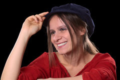 Portrait of a Smiling Young Caucasian Woman. Portrait of a young Caucasian woman smiling wearing a red shirt and a blue Gatsby cap (Selective Focus, Focus on the Royalty Free Stock Images
