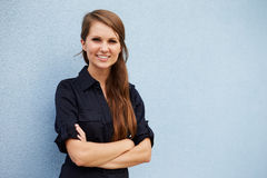 Portrait of smiling young Caucasian woman against grey wall Stock Photos