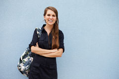 Portrait of smiling young Caucasian woman against grey wall Royalty Free Stock Photos
