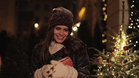 Portrait of Smiling Young Charming Girl wearing Winter Clothes, Looking Happy, Holding Gift Box, Walking in Falling Snow stock video
