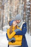 Portrait of smiling young couple in a bright clothes in a winter forest Royalty Free Stock Image