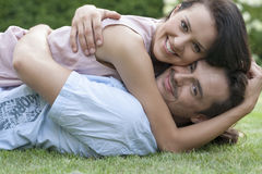 Portrait of smiling young couple embracing while lying in park Stock Photography