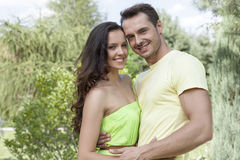 Portrait of smiling young couple embracing in park Stock Image