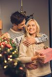 Smiling couple on christmas eve. Portrait of smiling young couple at home on christmas eve Royalty Free Stock Photography