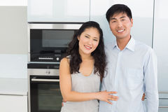 Portrait of a smiling young couple in the kitchen stock photo
