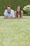 Portrait of smiling young couple lying side by side on grass in park Royalty Free Stock Images