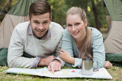 Portrait of a smiling young couple with map in tent Royalty Free Stock Images